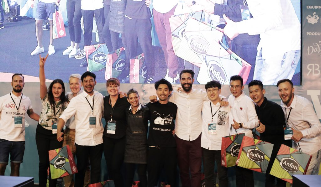 Twelve semi-finalists for the World Latte Art Championship stand in front of a large screen & stage wall.