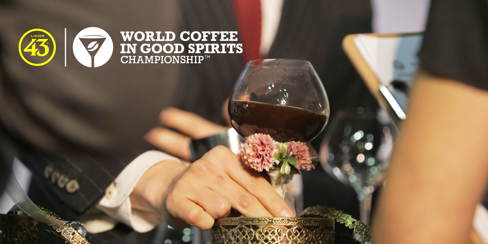 A squat piece of stemmed glassware decorated with dried flowers is served to a judge. There is a coffee cocktail in the cup. The image has the Licor 43 & World Coffee In Good Spirits Championships logos overlayed.